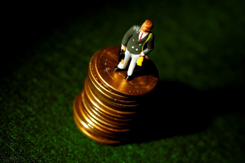Miniature man figure standing on coins